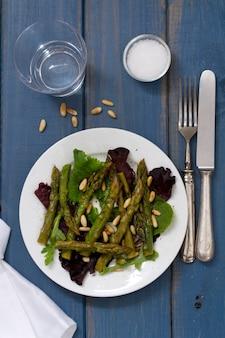 Salade aux anchois et à l'oignon sur une plaque blanche sur une surface bleue