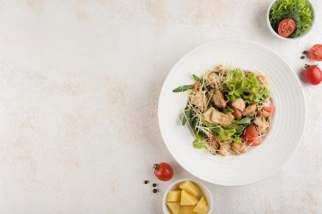 Salade aux fruits de mer. un mélange de laitue, roquette, tomates, calmars, crevettes, moules, sauce bisque sur une assiette blanche sur fond clair. vue de dessus avec un espace de copie pour le texte. orientation horizontale.