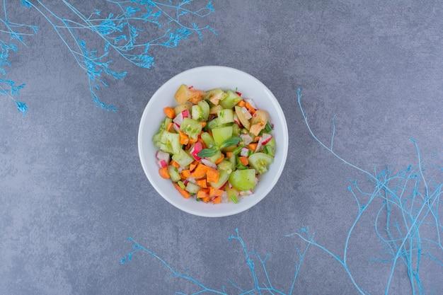 Salade aux herbes et légumes de saison dans un plat