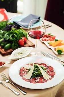 Salade aux herbes de pepperoni et parmesan tranché avec un verre de vin rouge.