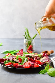 Salade aux tomates et feuilles de radicchio, basilic à l'huile d'olive et romarin. verser de l'huile d'olive