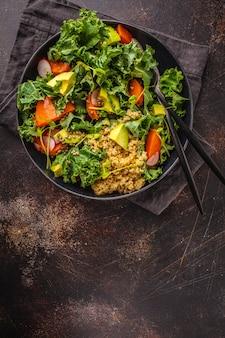 Salade d'avocat, de quinoa, d'igname et de chou frisé dans une assiette noire sur un fond sombre.