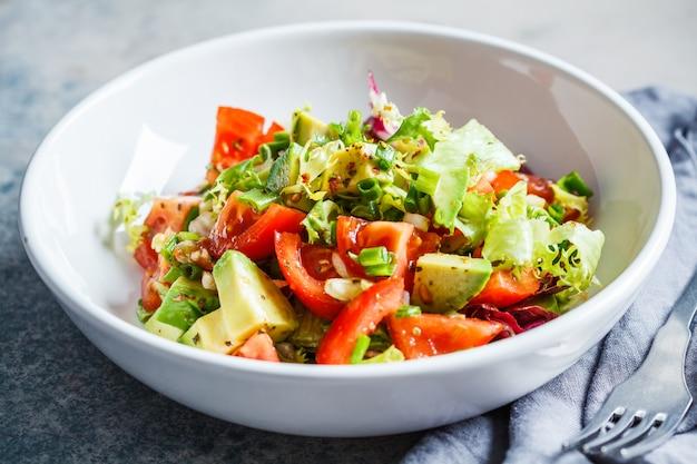 Salade d'avocat et de tomate dans un bol blanc. concept de nourriture végétalienne.