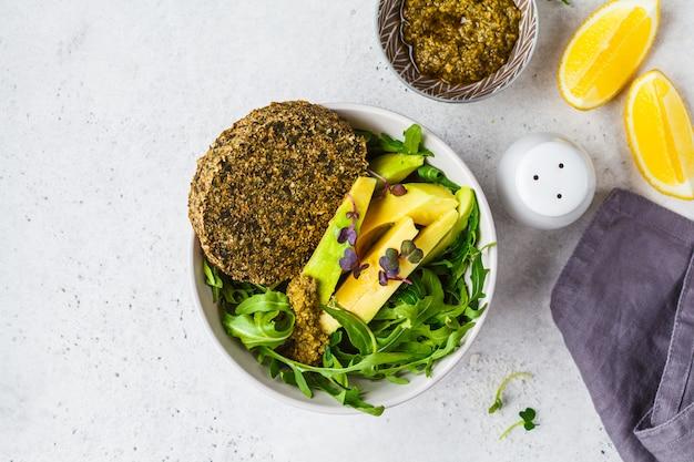 Salade d'avocat vert avec côtelette végétalienne verte, roquette et pesto dans un bol gris. concept de nourriture végétalienne saine.