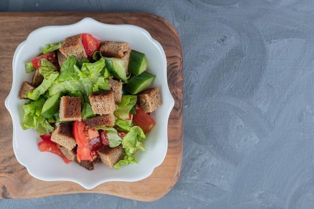 Salade de berger sur planche de bois sur table en marbre.