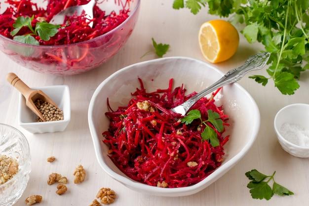 Salade de betterave végétalienne crue saine avec carotte et noix dans un bol