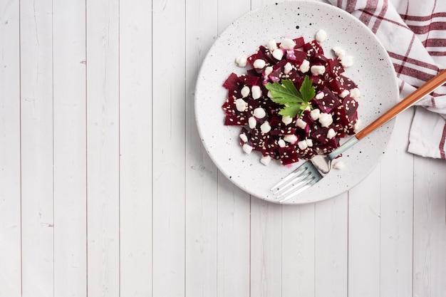 Salade de betteraves bouillies et caillé de grains aux graines de sésame sur une assiette.