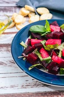 Salade de betteraves à l'huile d'olive et basilic dans une assiette sur fond de marbre blanc