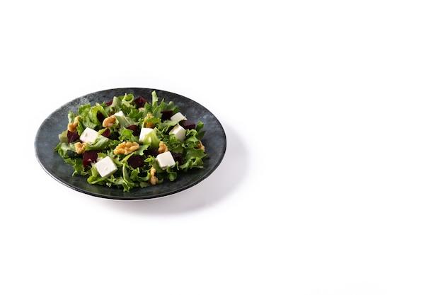 Salade de betteraves rouges au fromage feta, laitue et noix isolé sur fond blanc