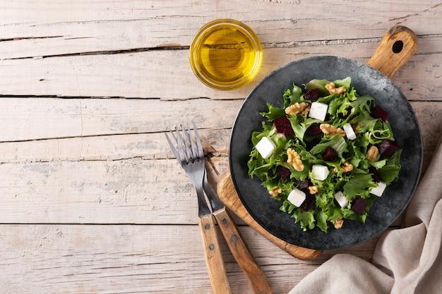 Salade de betteraves rouges au fromage feta, laitue et noix sur une table en bois rustique