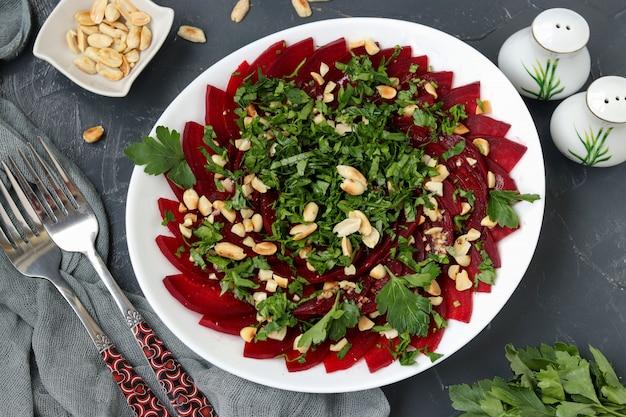 Salade de betteraves saines aux arachides et au persil sur une plaque blanche