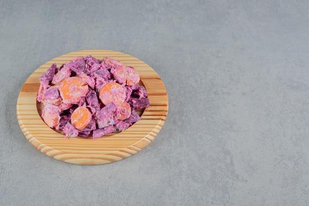 Salade de betteraves violettes et carottes sur une planche de bois.