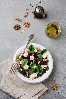 Salade de bettes, roquette, betterave, ricotta et noix avec de l'huile d'olive dans une vieille assiette en céramique sur une pierre grise ou une surface en béton vieilli