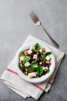 Salade de bettes, roquette, betterave, ricotta et noix à l'huile d'olive dans une vieille assiette en céramique sur une surface grise ou béton vieilli. mise au point sélective. vue de dessus.