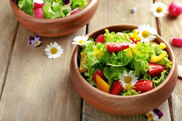 Salade biologique légère avec des fleurs, gros plan