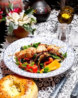 Salade de boeuf aux poivrons persil et huile d'olive garnie de morceaux de poulet sur des brochettes
