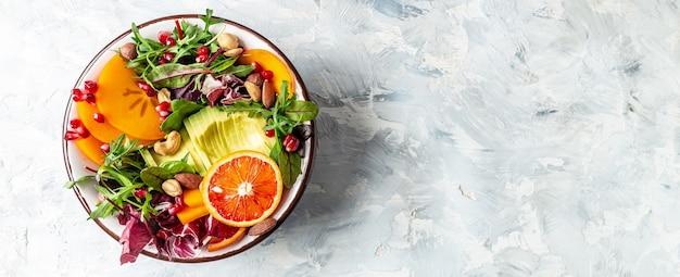 Salade de bol de bouddha végétarien sain avec fruits et légumes sur fond clair, format bannière longue, vue de dessus.