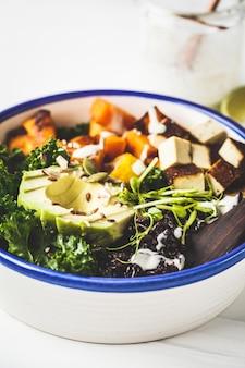 Salade de bouddha avec riz noir, avocat, tofu, vinaigrette à la patate douce, chou frisé et tahini