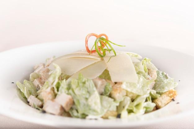 Salade caeser avec filet de poulet, assiette blanche, fond marron