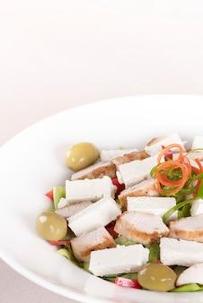 Salade caeser avec filet de poulet, assiette blanche