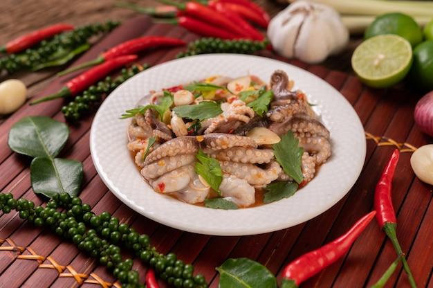 Salade de calamars à la coriandre, oignon vert haché, ail et maïs dans l'assiette