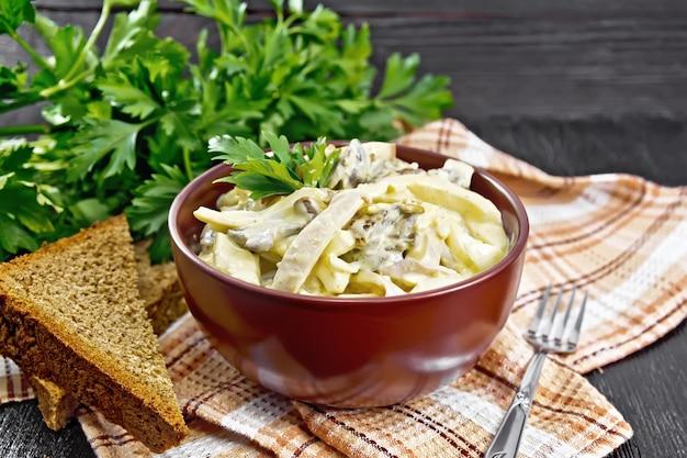 Salade de calmars, oeufs et champignons dans un bol sur une serviette, du pain, une fourchette et du persil sur fond de planche de bois