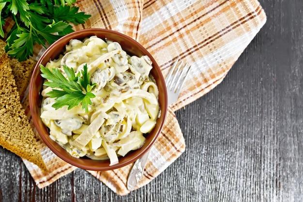 Salade de calmars, oeufs et champignons dans un bol sur une serviette, pain, fourchette et persil sur fond de planche de bois d'en haut