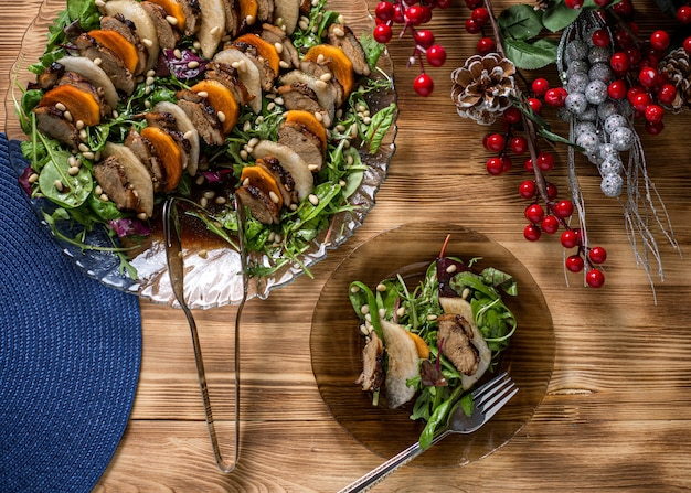 Salade de canard à la poire sur une table en bois, assaisonnée de pignons de pin
