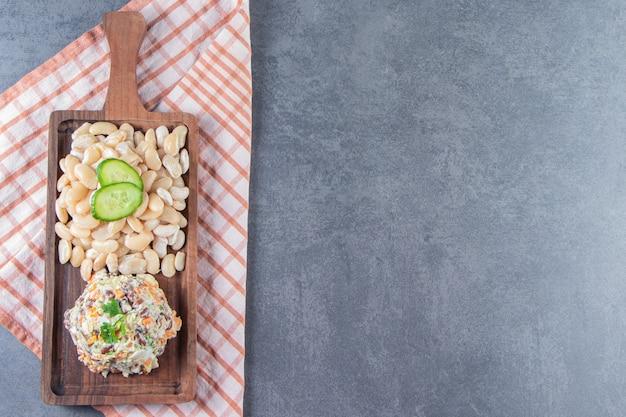 Salade capitale et haricots blancs au tableau sur une serviette, sur le fond de marbre.