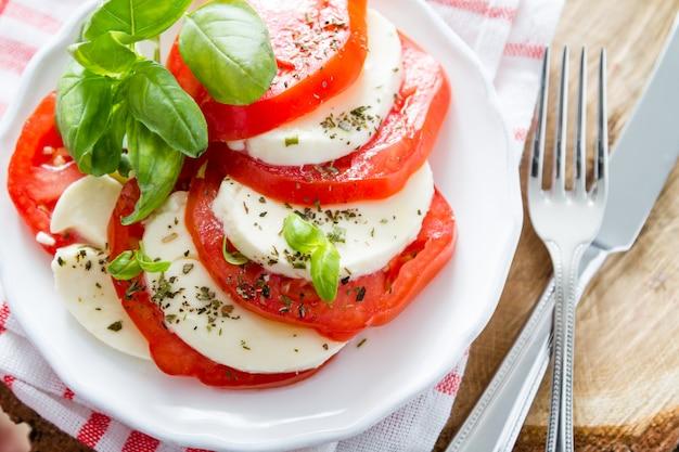 Salade caprese sur assiette blanche, gros plan