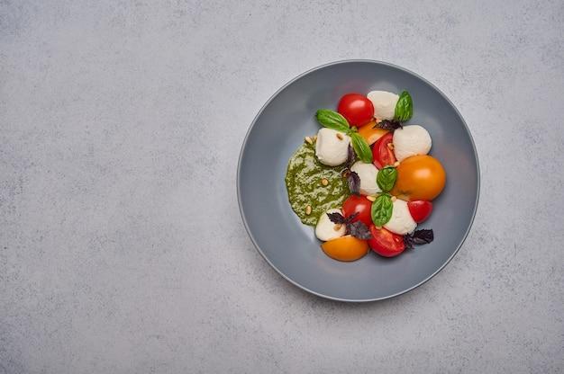 Salade caprese italienne aux tomates mûres, basilic au pesto et fromage mozzarella dans une assiette creuse grise