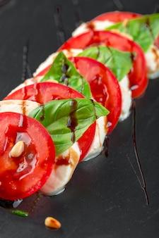 Salade caprese italienne fraîche avec mozzarella et tomates sur plaque noire