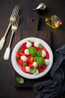 Salade caprese italienne traditionnelle avec tomates, fromage mozzarella et basilic dans une vieille assiette en céramique blanche. vue de dessus.
