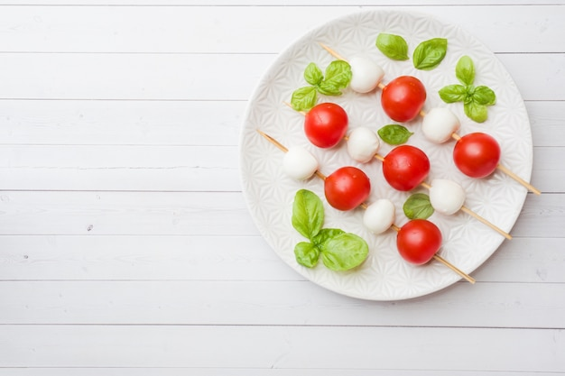 Salade caprese de tomates, fromage mozzarella et basilic sur une assiette blanche. cuisine italienne. espace de copie