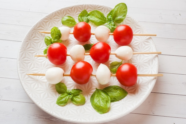 Salade caprese de tomates, fromage mozzarella et basilic sur une assiette blanche. cuisine italienne.