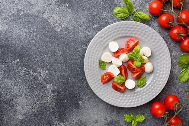 Salade caprese de tomates, fromage mozzarella et basilic. cuisine italienne. espace de copie