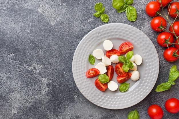Salade caprese de tomates, fromage mozzarella et basilic sur fond noir. cuisine italienne.