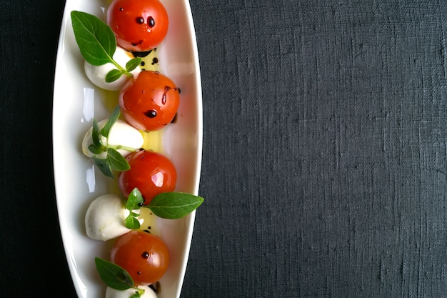 Salade caprese avec tomates mûres et mozzarella avec des feuilles de basilic fraîches. nourriture italienne.