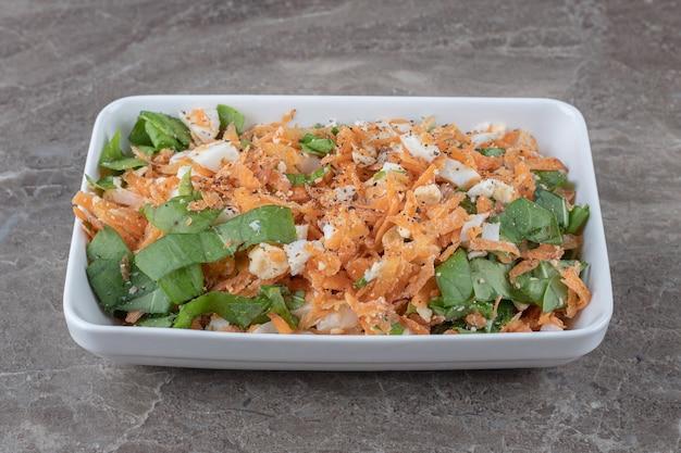 Salade de carottes tranchées sur plaque blanche.