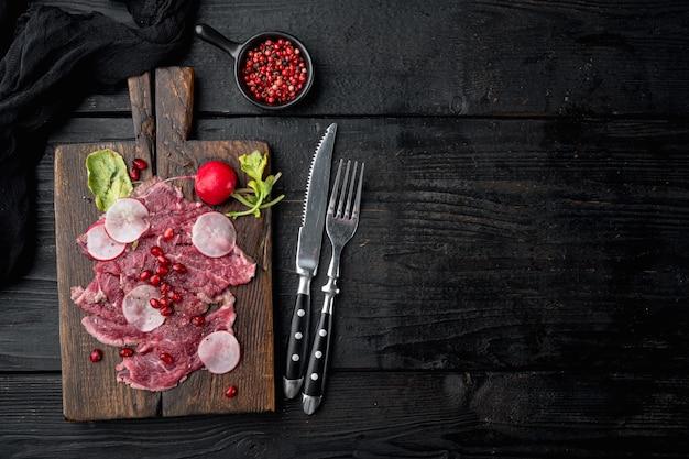 Salade de carpaccio frais avec du vinaigre de vin, avec radis et grenat, sur planche de service en bois, sur table en bois noir