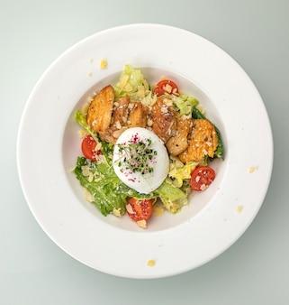 Salade césar sur une assiette blanche et une table blanche