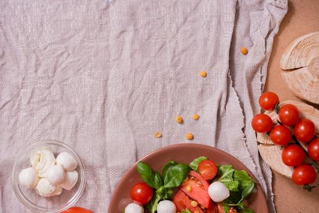 Salade césar au fromage mozzarella blanc et tomates cerises, basilic frais sur une serviette en lin gris.
