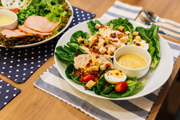 Salade césar au poulet grillé et santé avec fromage, croûtons, chêne vert, œuf à la coque et cris