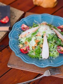 Salade césar au poulet avec laitue et tomates hachées au parmesan, craquelins dans la plaque d'immatriculation bleue.