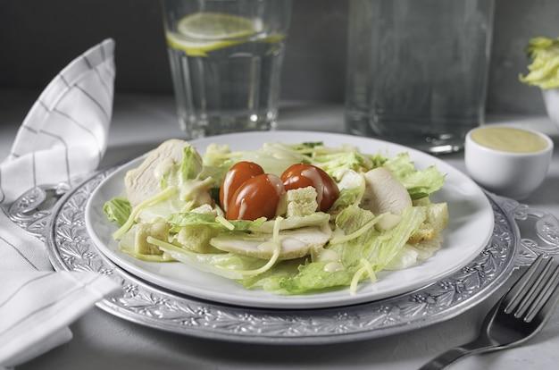 Salade césar au poulet et un verre d'eau sur fond gris