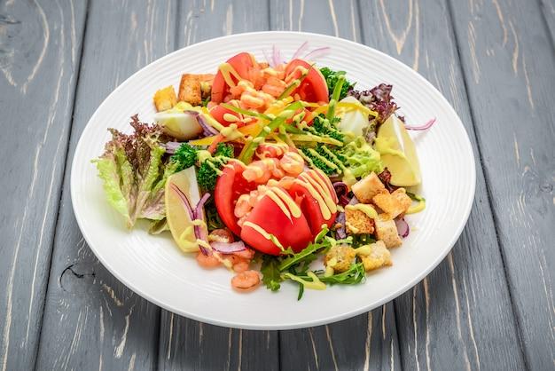 Salade césar aux fruits de mer avec crevettes, feuille de salade, croûtons, tomate cerise et fromage