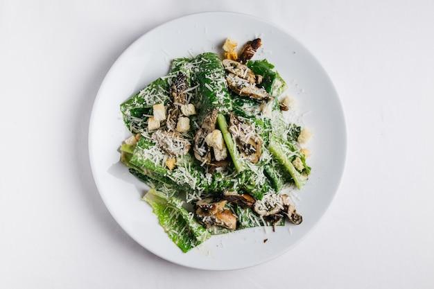 Salade césar aux huîtres servie dans une assiette blanche sur une nappe blanche