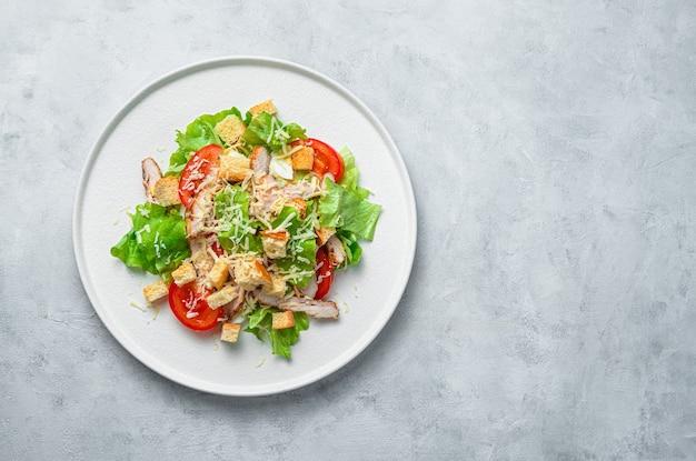 Salade césar classique avec poitrine de poulet sur fond gris. vue de dessus avec espace de copie. la nourriture saine.