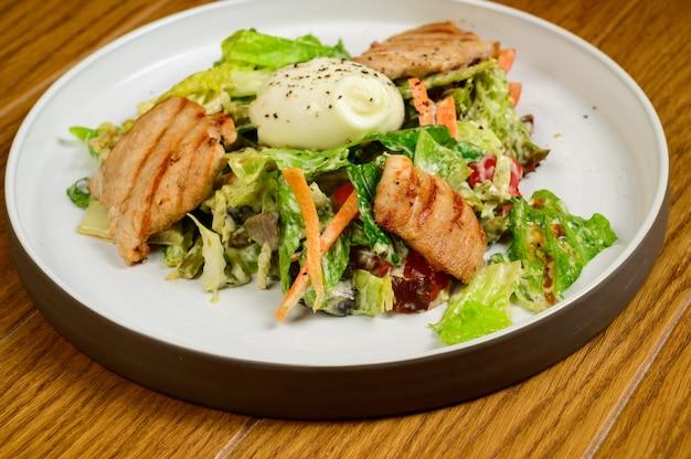Salade césar avec croûtons, œufs de caille, tomates cerises et poulet grillé dans une table en bois.délicieuse salade de poulet, noix, œuf et légumes.