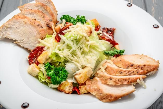 Salade césar avec croûtons, œufs de caille, tomates cerises et poulet grillé sur une table en bois